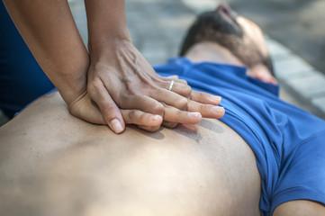 rianimazione cardiopolmonare con massaggio cardiaco su giovane svenuto a seguito di arresto cardiaco in un parco