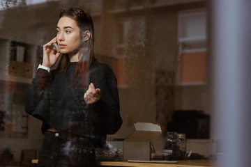 Female executive talking on mobile phone in office