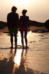 sunset silhouette of young couple in love holding hands at beach. Thailand. Khao Lak