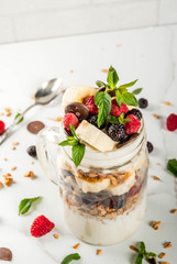 Summer fruit berry breakfast. Healthy banana split breakfast with cream cheese, raspberries, blackberries, mint, white and pink chocolate. In mason jar, marble table. Copy space close view