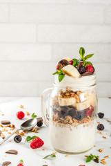 Summer fruit berry breakfast. Healthy banana split breakfast with cream cheese, raspberries, blackberries, mint, white and pink chocolate. In mason jar, marble table. Copy space