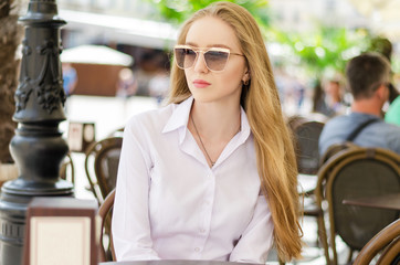 Outdoor summer portrait of young attractive lady in a cafe