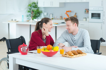 couple on a wheelchair eating the common meal indoors