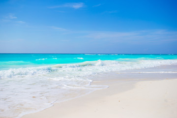 Idyllic tropical beach on Cuba in Caribbean with white sand, turquoise ocean water and blue sky