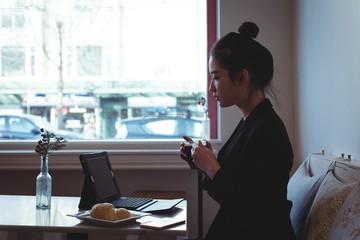 Woman having coffee while using digital tablet
