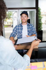 smiling delivery man and young woman signing clipboard