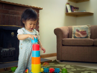 baby girl playing stacking cups at home