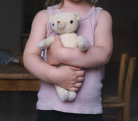 Kleines Mädchen hält ihren Teddybären fest im Arm