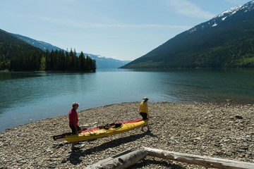 Couple carrying kayak while walking lakeshore
