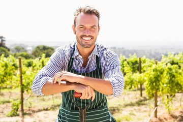 Portrait of young man with shovel at vineyard