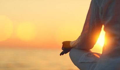 Wall Mural - hands of woman meditating in yoga pose at sunset on beach