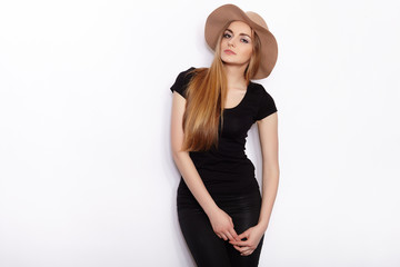 Young beautiful fashion model in women black t-shirt trendy hat black torn jeans posing in studio against white background