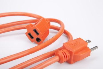 Bright orange extension cord on a white surface. Orange extension cable isolated on white background.