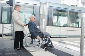 senior woman pushing man in wheelchair