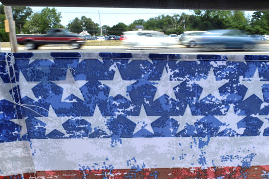 Cars pass eastward in a blur as framed through a beach chair in Toms River, New Jersey