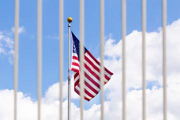 The USA flag visible through fence grates