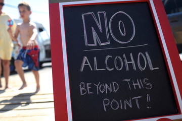 "A boy with an ice cream walks past a sign stating ""No Alcohol Beyond This Point!"" in Seaside Park, New Jersey"