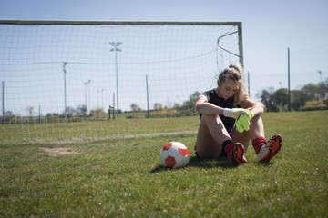 Tired soccer player sitting on field