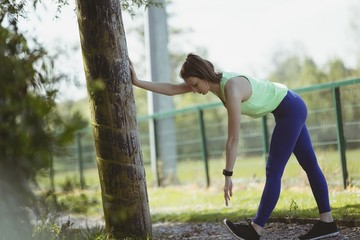 Side view of woman exercising by tree