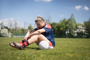 Soccer player sitting with ball on playground