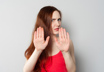 A frightened annoyed young woman holds her hands in front of her making stop sign, defending herself from someone or pushing someone away
