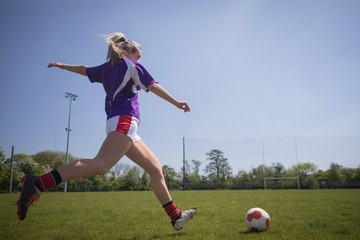 Full length of woman playing soccer on field