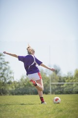 Rear view of woman kicking soccer ball
