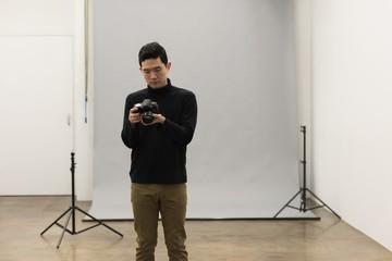 Male photographer adjusting camera