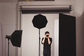 Male photographer photographing at studio