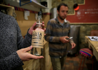 "Felipe Marin no pictured holds  a bottle of ""Killa Moonshine"" drink a handcrafted drink, La Paz"