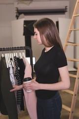 Beautiful woman choosing clothes hanging on rack