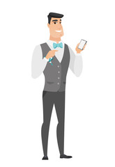 Caucasian groom holding a mobile phone.