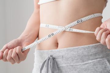 ウェストサイズをメジャーで測る女性