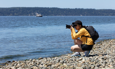 Woman nature photographer working on photos near shoreline of ocean