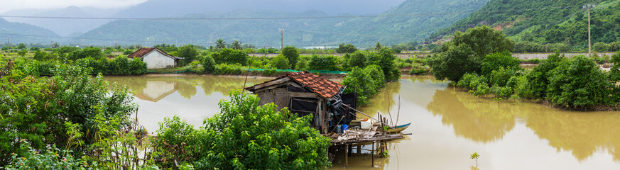 House among field near river in rain water season