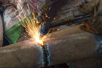A worker uses a oxygen acetylene cutting
