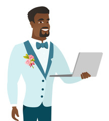 Young african-american groom using a laptop.