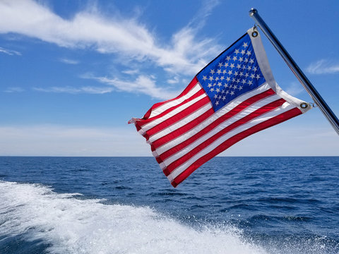 American flag on boat with boating wake on Lake Michigan