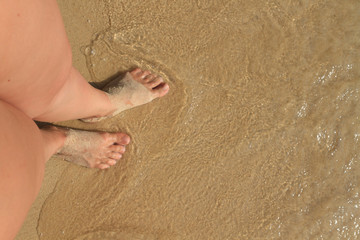 Female feet in the sand. on top of female feet on a sandy beach with footprints