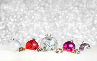 Christmas decoration ball on white fur at silver bokeh light background,Holiday greeting card