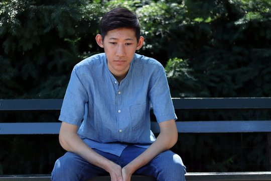 Young sad asian man sitting on park bench looking down
