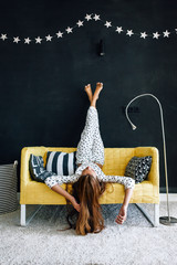 Pre teen child on the couch against black wall in modern living room interior