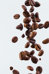 Falling grains of roasted coffee on a white background