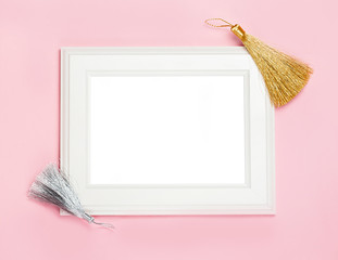 white wooden frame on pink background decorated with Decorative brush, blank space for a text. Top view, flat lay