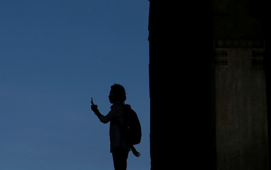 A man uses his cell phone to take pictures next to a building in Colombo