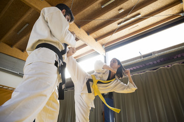 Young man and woman in kimonos practicing hapkido attacks in gym.