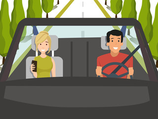 man driving car while woman playing phone