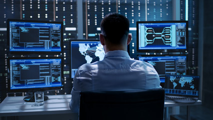 System Security Specialist Working at System Control Center. Room is Full of Screens Displaying Various Information. Wall mural