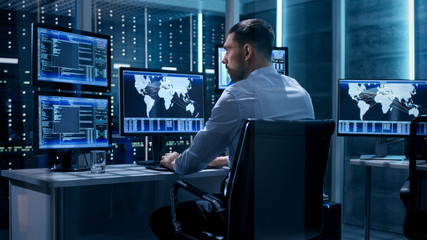 Technical Controller Working at His Workstation with Multiple Displays. Displays Show Various Technical Information. He's Alone in System Control Center. Wall mural