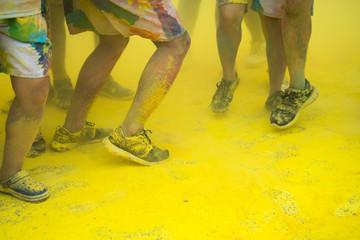 People dancing at an color run event closeup at legs